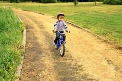 une petite fille conduit un vélo en stationnement Photos stock