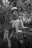 Une petite fille congelée s'assied sur un tronçon nu-pieds Image noire et blanche photos libres de droits