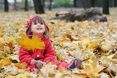 Une petite fille dans des feuilles jaunes photographie stock