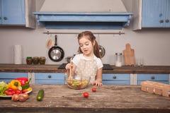 Une petite fille dans la salade de mélanges de cuisine avec une grande cuillère en bois images stock