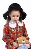 Une petite fille dans le chapeau joue avec un ours de nounours Photographie stock libre de droits