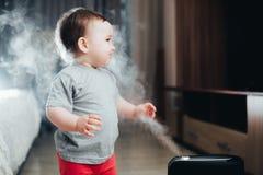 Une petite fille dans le pantalon rouge regarde et touche l'humidificateur Humidité dans le concept de maison image libre de droits