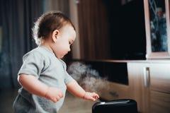 Une petite fille dans le pantalon rouge regarde et touche l'humidificateur Humidité dans le concept de maison photos stock