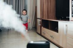Une petite fille dans le pantalon rouge regarde et touche l'humidificateur Humidité dans le concept de maison photos libres de droits