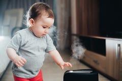 Une petite fille dans le pantalon rouge regarde et touche l'humidificateur Humidité dans le concept de maison images stock