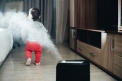 Une petite fille dans le pantalon rouge regarde et touche l'humidificateur Humidité dans le concept de maison photographie stock libre de droits