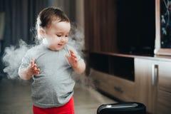 Une petite fille dans le pantalon rouge regarde et touche l'humidificateur Humidité dans le concept de maison photo stock
