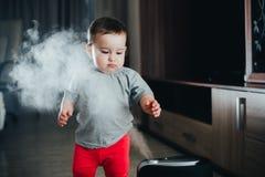 Une petite fille dans le pantalon rouge regarde et touche l'humidificateur Humidité dans le concept de maison images libres de droits
