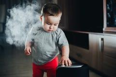 Une petite fille dans le pantalon rouge regarde et touche l'humidificateur Humidité dans le concept de maison image stock