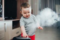 Une petite fille dans le pantalon rouge regarde et touche l'humidificateur Humidité dans le concept de maison photographie stock