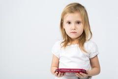 Une petite fille dans un blanc vêtx tenir le contrôleur de jeu Image stock