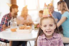 Une petite fille dans un chapeau de fête pose dans la perspective de la famille qui s'assied derrière elle à la table de fête Photographie stock libre de droits