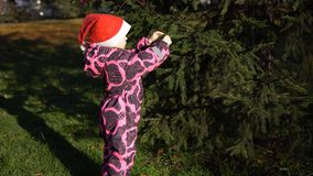Une petite fille dans un chapeau de Santa Claus décore des boules un arbre dans la rue banque de vidéos