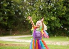 Une petite fille dans un costume lumineux chassant des bulles Photo stock