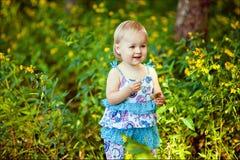 Une petite fille dans une robe bleue souriant tout en se tenant dans les gras image libre de droits