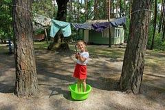 Une petite fille de sourire avec deux tresses se tient dans la cuvette de blanchisserie et joue avec l'arme à feu d'eau image stock