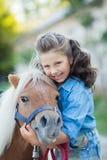 Une petite fille de sourire avec les cheveux bouclés s'est habillée dans des jeans marchant avec un poney à l'écurie photographie stock libre de droits