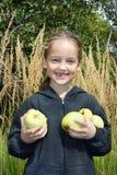 Une petite fille de sourire sans prises de foretooth dans des ses mains beaucoup de pommes photographie stock