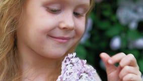 Une petite fille dehors en parc ou jardin tient les fleurs lilas Buissons lilas ? l'arri?re-plan ?t?, parc clips vidéos