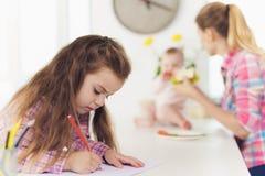 Une petite fille dessine sur le dessus de cuisine avec les crayons colorés La mère de la fille avec le bébé prépare un sandwich Images stock