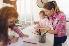 Une petite fille dessine sur le dessus de cuisine avec les crayons colorés La mère d'une fille avec un bébé s'assied côte à côte Photos libres de droits