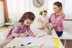 Une petite fille dessine sur le dessus de cuisine avec les crayons colorés La mère d'une fille avec un bébé s'assied côte à côte Image libre de droits