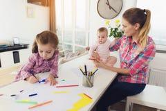 Une petite fille dessine sur le dessus de cuisine avec les crayons colorés La mère d'une fille avec un bébé s'assied côte à côte Photo stock