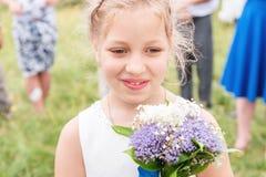 Une petite fille douce dans une robe de mariage et avec un bouquet dans des ses mains Photo libre de droits