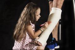 Une petite fille drawning sur la fonte de plâtre Photographie stock libre de droits