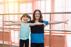 Une petite fille et sa mère font des sports Images stock