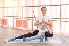 Une petite fille et sa mère font des sports Image libre de droits