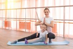 Une petite fille et sa mère font des sports Photos stock