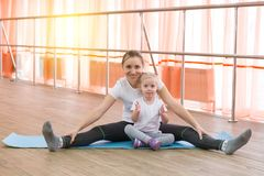 Une petite fille et sa mère font des sports Photographie stock