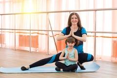 Une petite fille et sa mère font des sports Image stock