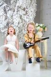 Une petite fille et un musicien de bruit avec la guitare s'asseyent sur des lettres Image stock