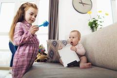 Une petite fille et un nourrisson jouent La fille tenant un jouet dans des ses mains, le bébé a juste joué avec le comprimé Images stock