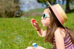 Une petite fille faisant des bulles de savon Image libre de droits