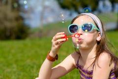 Une petite fille faisant des bulles de savon Images libres de droits