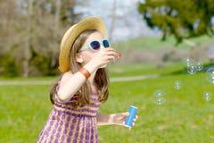 Une petite fille faisant des bulles de savon Photo stock