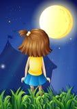Une petite fille faisant face au fullmoon lumineux Photo stock