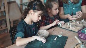 Une petite fille fait un métier d'argile dans un atelier de poterie La maman et l'enfant passent le temps effectuant ensemble le  banque de vidéos
