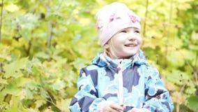Une petite fille gaie se tient dans les buissons et rit d'un air provoquant clips vidéos