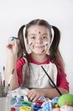 Une petite fille heureuse peignant des oeufs de pâques Photos libres de droits