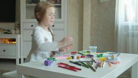 Une petite fille joue avec de la pâte à modeler, la roule avec ses mains et les coupes une figure, des figures et des crayons col clips vidéos
