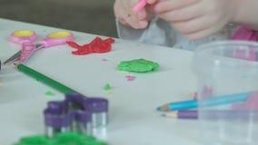 Une petite fille joue avec de la pâte à modeler, sculpte une figure, là est des figures et des crayons colorés sur le bureau, clips vidéos