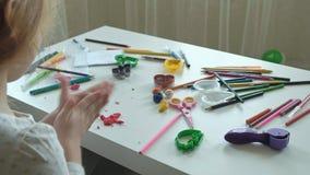 Une petite fille joue avec de la pâte à modeler, sculpte une figure, là est des figures et des crayons colorés sur le bureau, banque de vidéos