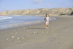 Une petite fille joue sur la plage photographie stock libre de droits