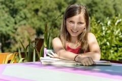 Une petite fille lit un livre Photographie stock