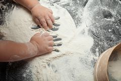 Une petite fille malaxe la pâte de la farine pour faire cuire les gâteaux faits maison, un plan de crâne, l'espace pour le texte images stock