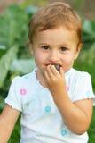 Une petite fille mangeant le plomb Photographie stock libre de droits